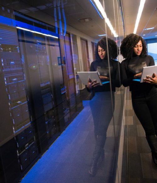 woman-holding-laptop-beside-glass-wall-1181316-1024x683
