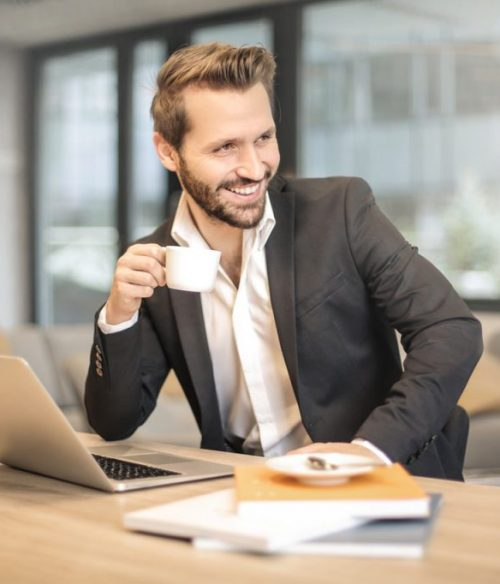 man-holding-white-teacup-in-front-of-gray-laptop-842567-1024x682